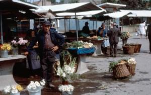 Comercianţi, în piaţa Cipariu: în prim plan vânzători de flori; în plan secund hoştezeni cu produse din grădinile proprii (sursa: flikir.com)